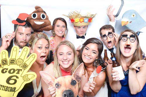 Silly guests of a wedding take pictures in the photo booth